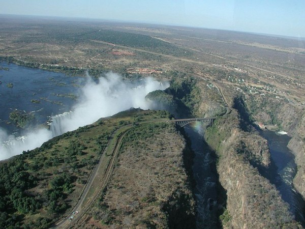 """Here's a view of Victoria Falls from the helicopter. (You'll probably want to click the image to see a larger picture, where you'll find this caption waiting for you at the bottom.) At the left the broad Zambezi plunges 100 metres into the first gorge, raising the eternal cloud of mist and forming a rainbow visible in front of the bridge across the gorge. We're overflying Zimbabwe at the moment; the ""Knife Edge"" from which the first photo of the falls above was taken protrudes from the Zambia side above and to the left of the bridge. The bungee jumping platform is visible at the centre of the bridge, near the top of the rainbow. Electricity generation in Zambia is in excess of 99% hydroelectric; a power station is visible at the right of the image, along with outflow from the turbines into the gorge. After the falls, the Zambezi traverses a series of zigzag gorges, the first two of which are visible here."" Photo and words by John Walker (2001)"