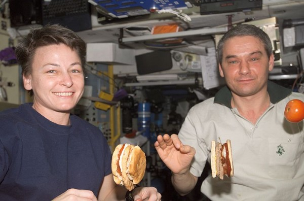 View of Astronaut Peggy Whitson, flight engineer (left) and Cosmonaut Valery Korzun, commander (right), eating a meal in the Service Module (SM)/Zvezda. Tomato and hamburger are floating. Photo by NASA.