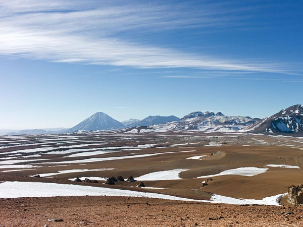 The mountainous scenery of Chile's Chajnantor Plateau, with snow and ice scattered over the barren terrain. Photo by the ALMA.